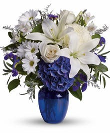 White lilies and roses and blue hydrangeas in a cobalt blue vase