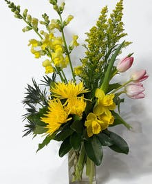 yellow and pink spring flowers in a cylinder vase