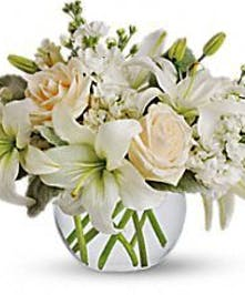 White lilies and roses in a clear bubble bowl vase.