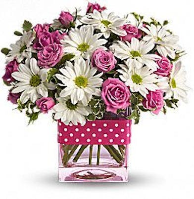 White daisies and pink roses in a cube vase tied with polka dotted ribbon