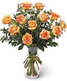 One dozen orange Tropicana roses in a clear glass vase
