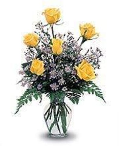 Six yellow roses and fillers in a clear glass vase