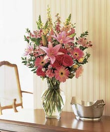 A variety of pink flowers in a tall clear glass vase