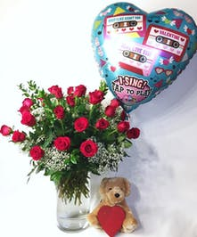 three dozen roses in tall cylinder vase with a heart shaped singing balloon, heart box of chocolates and a stuffed animal