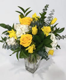 Tall rectangular  vase with yellow roses and daffodils, white hydrangea and blue thistle.