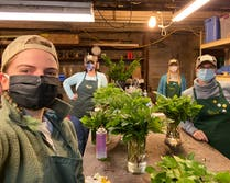 Four of our designers, each wearing COVID masks, hard at work in the plant shop