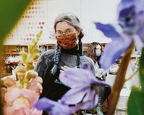 Partially obscured by purple and yellow blooms, one of our team members smiles at the camera